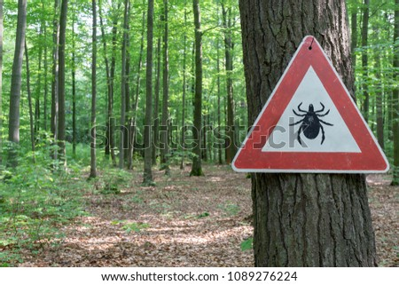 tick insect warning sign in forest #1089276224