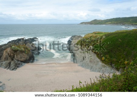 Sheltered beach in Woolacombe on a cloudy summer day #1089344156