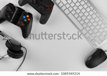 Gamepads, mouse, headphones and keyboard on table #1089349214
