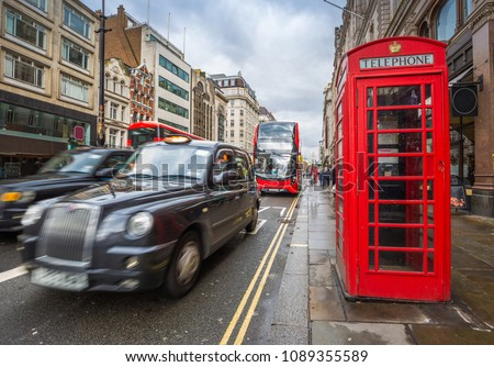 London, England - Iconic red double-decker buses on the move with traditional red telephone box in the center of London at daytime #1089355589