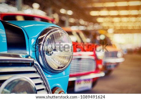 Close-up of headlights of red vintage car in a row.  Royalty-Free Stock Photo #1089491624