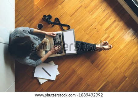 Top view photo of a woman using credit card for online payment via portable computer while sitting on a floor with a dog. Young hipster girl booking flight tickets online via laptop. #1089492992
