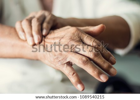 Close up hands of senior elderly woman patient suffering from pakinson's desease symptom. Mental health and elderly care concept #1089540215