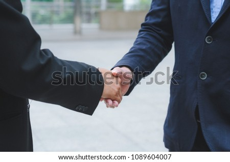 attractive business man shaking hand for complete deal together business successful at outdoor in city. teamwork concept. partnership concept and dealership concept. #1089604007