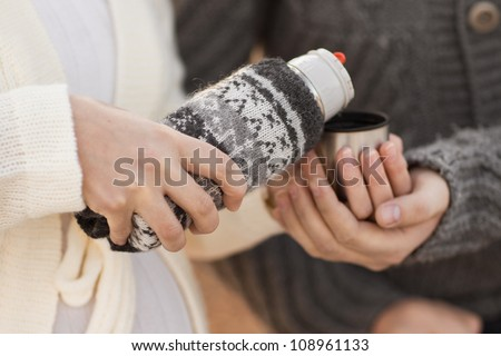 woman pours tea from a thermos. #108961133