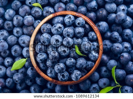 Fresh blueberry with drops of water in wooden bowl. Top view. Concept of healthy and dieting eating #1089612134