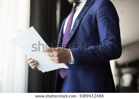 Two financial documents in hands of elegant and contemporary financier working in office #1089612488