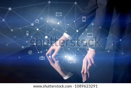 Male hands touching interactive table with blue mixed communication icons in the background #1089623291