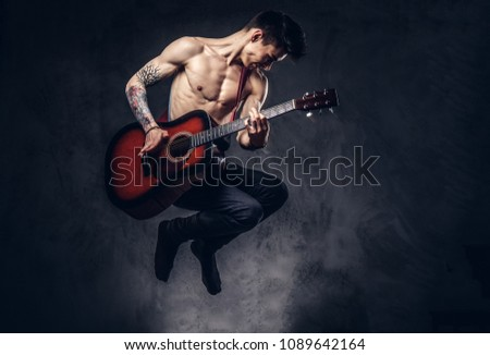 Handsome shirtless young musician playing guitar while jumping. #1089642164