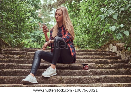 Young blonde hipster girl using a smartphone while sitting on steps in a park. #1089668021
