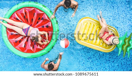 Happy friends playing with air lilo ball inside swimming pool - Young people having fun on summer holidays vacation - Travel, holidays, youth lifestyle, friendship and tropical concept #1089675611