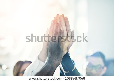 Diverse team of positive businesspeople standing in a huddle together in a bright modern office high fiving each other   #1089687068