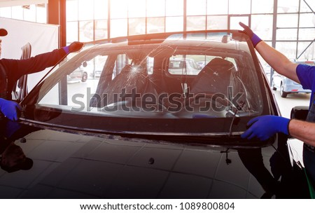 Automobile special workers remove old windscreen or windshield of a car in auto service station garage. Background Royalty-Free Stock Photo #1089800804