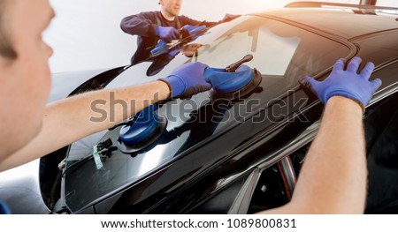 Automobile special workers replacing windscreen or windshield of a car in auto service station garage. Background #1089800831