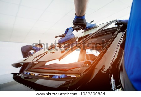 Automobile special workers replacing windscreen or windshield of a car in auto service station garage. Background #1089800834