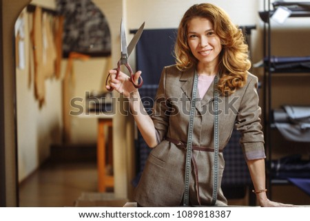 Portrait of pretty smiling adult fashionable dressmaker female with tailor scissors at studio #1089818387