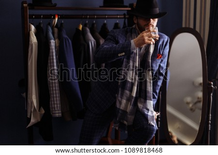Elegant man in fashion suit and hat putting on his eyes choosing new suit at men's clothing boutique, drinking beverage. Men's beauty, fashion. #1089818468