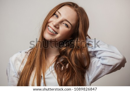 Happy young red-haired woman in braces smiling on white background looking at camera #1089826847