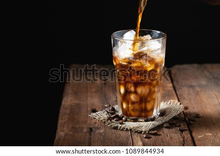 Ice coffee in a tall glass over and coffee beans on a old rustic wooden table. Cold summer drink on a dark background with copy space. The process of pouring drink from a coffee pot into a glass #1089844934