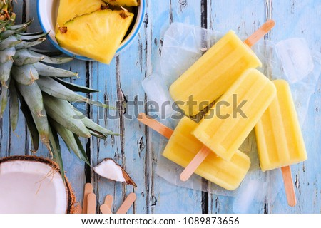 Pineapple coconut popsicles in a cluster. Top view scene over a blue wood background. #1089873656