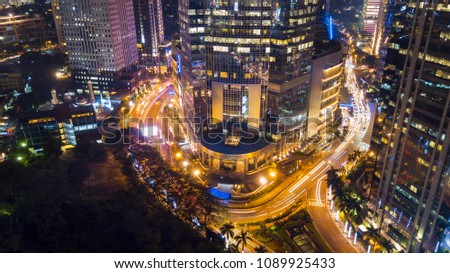 JAKARTA - Indonesia. May 08, 2018: Top view of beautiful glow lights on the highway and modern skyscrapers at night time #1089925433
