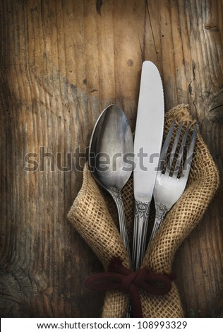Vintage silverware on rustic wooden background. Top view of kitchen cutlery setting on grunge restaurant table. #108993329