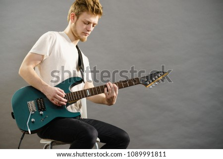 Young bearded man with electric guitar. Adult person is holding instrument and playing. Hobby, music concept, on grey #1089991811