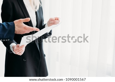 communication and interaction between business coworkers. data exchange. hand pointing to important piece of information in document #1090001567
