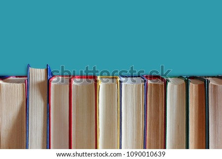 Books in hardcover on a blue background. Library, education, literature. Bookshelf. #1090010639