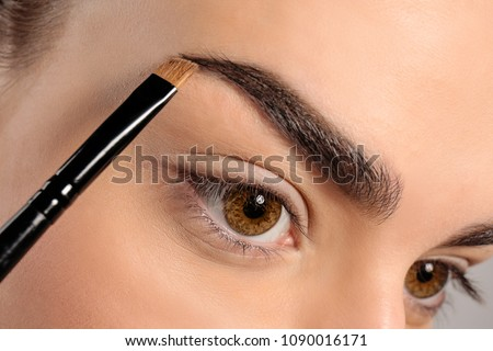 Young woman correcting eyebrow shape with brush, closeup Royalty-Free Stock Photo #1090016171