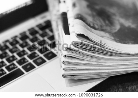 Newspapers and laptop. Pile of daily papers with news on the computer. Pages with headlines, articles folded and stacked on keypad of electronic device. Modern gadget and old journals, focus on paper Royalty-Free Stock Photo #1090031726