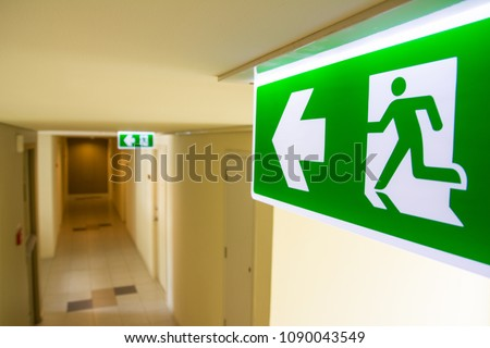 Fire exit sign at  the corridor in building Royalty-Free Stock Photo #1090043549
