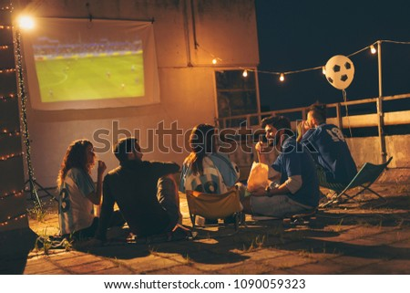 Group of young friends having fun while watching a football match on a building rooftop. Focus on the guy eating popcorn #1090059323