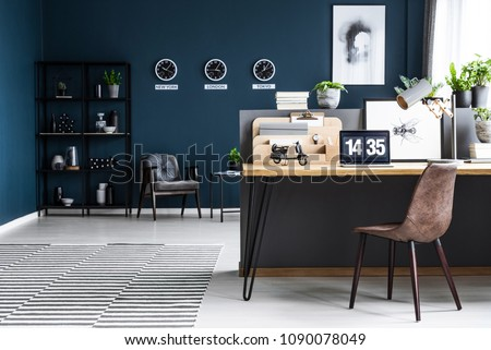 Classy, dark blue home office interior for a global businessman with elegant furniture and a computer on a wooden desk #1090078049