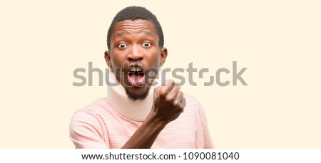 Injured african black man wearing neck brace irritated and angry expressing negative emotion, annoyed with someone #1090081040