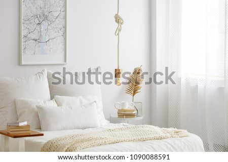Simple bulb lamp on a rope hanging above bed with white bedclothes, books and gold fern leaf on an end table in white bedroom interior #1090088591