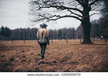 Rural scene with woman in hat walking on field, melancholic autumn mood #1090090970
