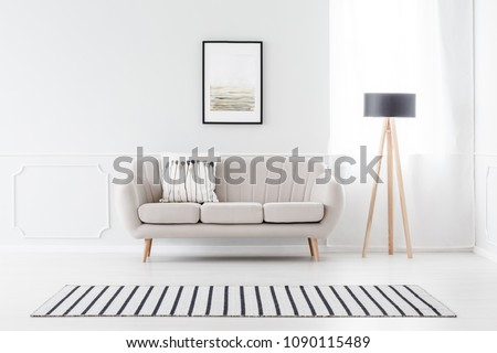 Beige couch standing against white wall with molding and watercolor poster in cozy living room interior #1090115489