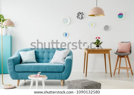 Comfy sofa, coffee table, pouf, wooden table and chair, and hanging patterned plates in a sweet living room interior #1090132580