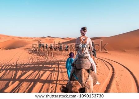 Girl riding a camel in Sahara Desert Morocco. Camel expedition in the desert. #1090153730