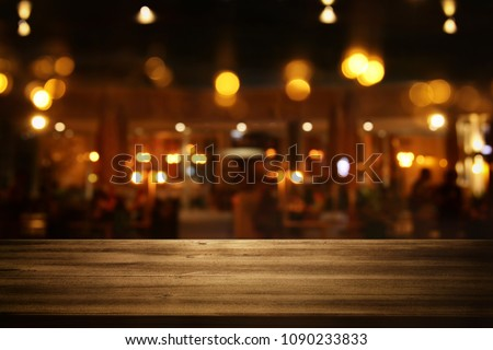 Image of wooden table in front of abstract blurred restaurant lights background #1090233833