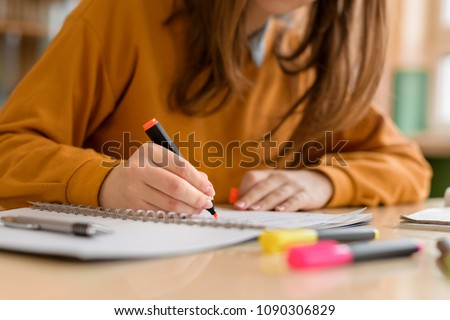 Young unrecognisable female college student in class, taking notes and using highlighter. Focused student in classroom. Authentic Education concept. Royalty-Free Stock Photo #1090306829