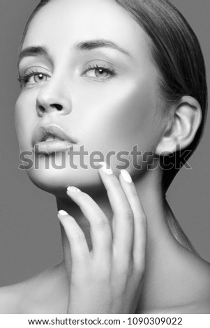 Beauty face of fashion model girl. Hand near clean skin, natural lips, nude make-up. Skincare facial treatment concept. Black and white #1090309022
