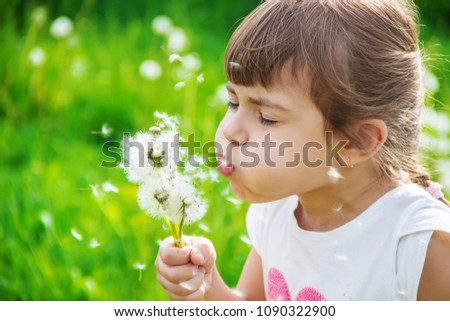 girl blowing dandelions in the air. selective focus. #1090322900