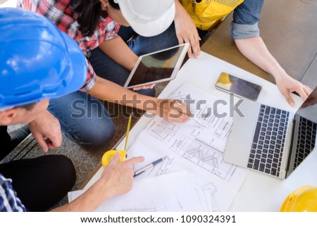 multiethnic diverse team of engineers discussing about new project in city, engineer man and woman work with blueprint in front of building, business people co-working teamwork concept,focus on hand #1090324391