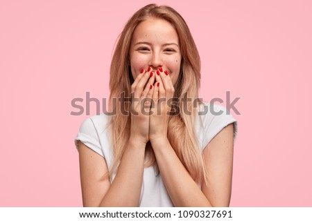 Horizontal shot of good looking young female giggles joyfully, covers mouth as tries stop laughing, wears casual white t shirt isolated on pink background. Happy woman recieves proposal from boyfriend #1090327691