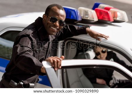 happy young police officers with car looking at camera