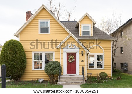 Yellow single family home with red door and floral wreath #1090364261