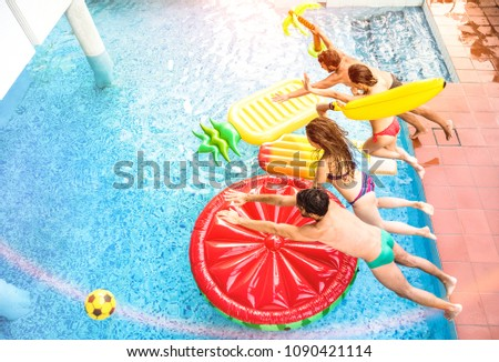Top view of active friends jumping at swimming pool party - Vacation concept with happy guys and girls having fun in summer day at luxury resort - Dynamic young people on warm bright sunshine filter #1090421114