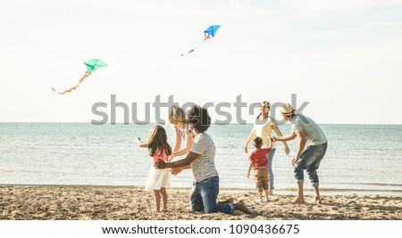 Group of happy families with parent and children playing with kite at beach vacation - Summer joy carefree concept with mixed race people having fun together at sunset - Bright vintage filter #1090436675